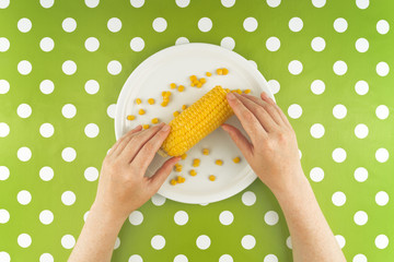 Woman eating maize corn, top view
