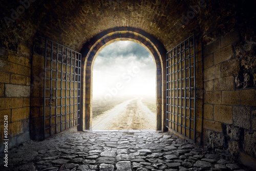 Tuinposter Historisch geb. Gate opening to endless road leading nowhere