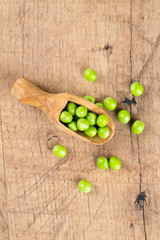 fresh pea pods in a wooden scoop