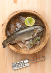 Raw trout fish with ice in wooden bowl