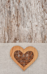 Wooden decorative heart on the linen fabric and old wood
