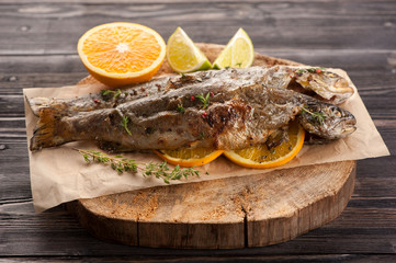 Baked trout fish with orange and herbs on wooden background