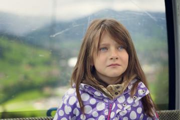 Trauriges kleines Mädchen sitzt in einer Kabinenseilbahn