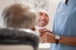 Dentist showing patient his new smile in the mirror - 69364822