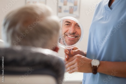 Leinwandbild Motiv Dentist showing patient his new smile in the mirror