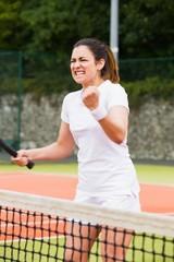 Pretty tennis player celebrating a win