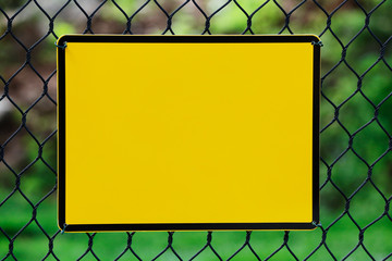 Blank yellow info plate hung on a wire fence
