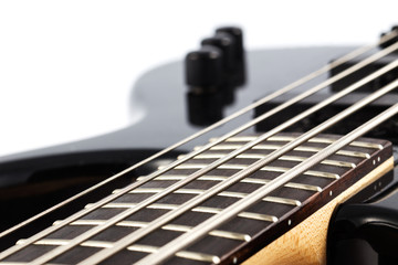 Detail picture of an electric bass guitar on white background