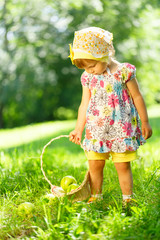 Little girl on grass with basket of apples