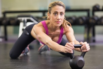 Serious woman lifting kettle bell in gym