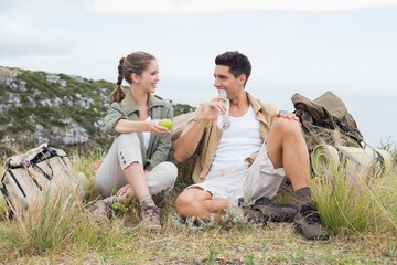 Couple taking break after hiking uphill