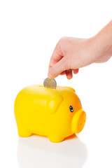 Yellow piggy bank is getting two euro coin from a hand
