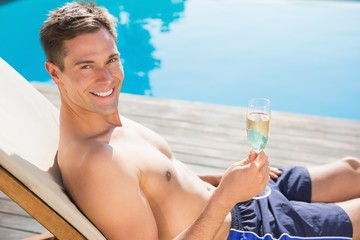 Man holding champagne flute by the swimming pool