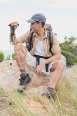 Hiking man sitting on mountain terrain