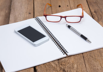 Notebook and eyeglasses on old wooden background