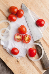 Red small tomatoes on wood board.