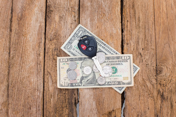 Car remote key with dollar money on wood background