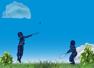 children playing badminton in green grass
