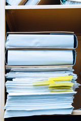 Stack of paper in bookcase