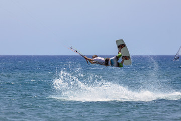 a boy engaged in an acrobatic leap to kitesurf