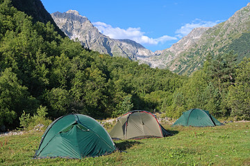 Three camping tents between the mountains