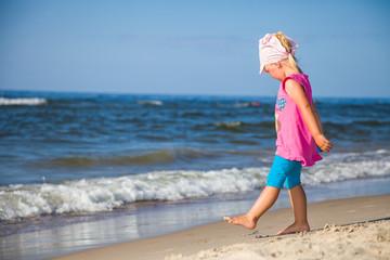 Infant preschool girl playing on a beach