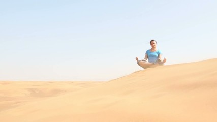 young woman doing yoga in the desert