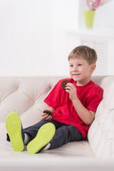 Portrait of kid sitting in white sofa.