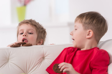 Portrait of two kids eating in white sofa.