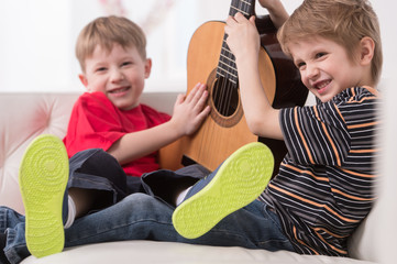 two caucasian boys playing with acoustic guitar.