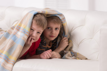 Two children looking into camera under blanket.