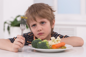 little blond boy eating at kitchen.