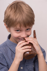 Child licks chocolate glaze from jar.