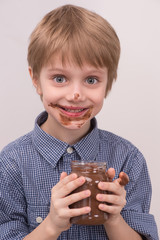 Smiling kid eating chocolate from jar.