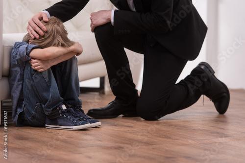 Father kneeling and comforts sad child. - 69371607