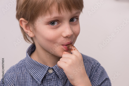 Child licks chocolate glaze with finger. - 69371654