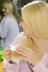 Frau im Schlafanzug trinkt Kaffee am Morgen