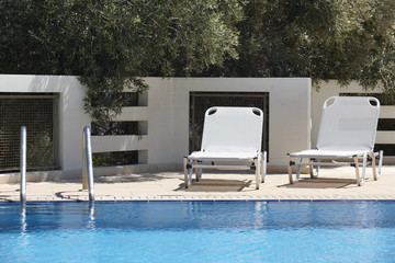 White sunbeds and swimming pool in summer