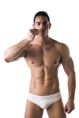 Muscular man removing tape from mouth