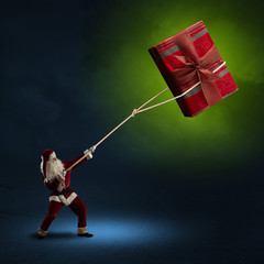 Santa Claus pulls a box with a gift