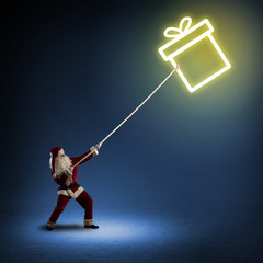 Santa Claus pulls a symbol box with a gift