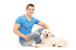 Man chilling out with his puppy seated on floor