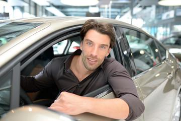 junger attraktiver Mann im Autohaus // young man in the car