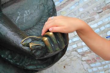 рука девушки на руке скульптуры