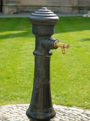 Black metal drinking fountain with brass tap