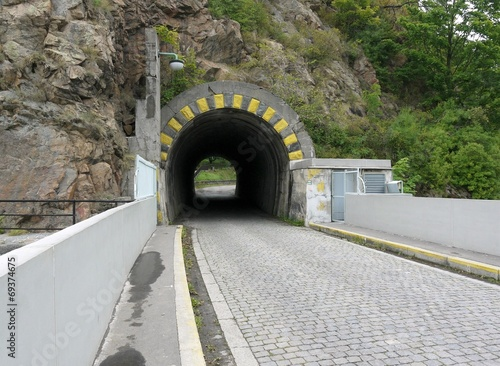 Small and short road tunnel in stone rock - 69374675