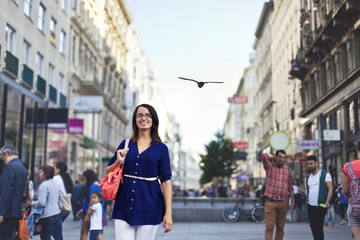 Cheerful urban girl standing out from the crowd at a city street