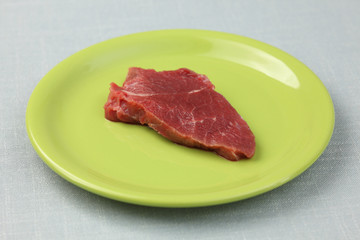 Raw fillet beef steak on a green plate