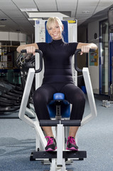 Reife Frau im Fitness Studio an Trainingsgerät Brustmaschine