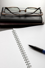 blank notebook and glasses